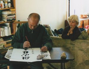 Xing Yi Quan Grand Master Liang Ke Quan writes calligraphy while Connor observes intently